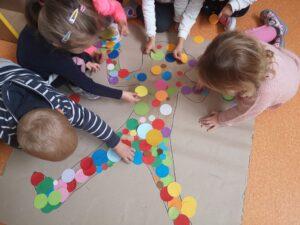 dzieci wyklejają sylwetę dziecka kołami