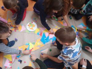 dzieci wyklejają sylwetę dziecka trójkątami