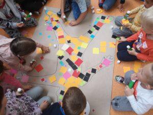 dzieci wyklejają sylwetę dziecka kwadratami